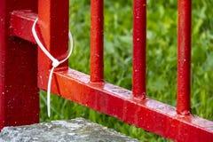 白色塑料手铐和红色庭院铁篱芭 库存照片