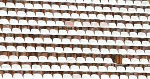 白色塑料椅子在橄榄球体育场内  库存图片