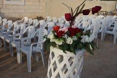 白色塑料椅子连续和玫瑰花束婚礼的 免版税库存图片