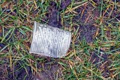 白色塑料玻璃在草说谎本质上 免版税库存照片