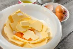 白色塑料碗用黄油、蛋黄和糖混合了-预习功课 免版税库存照片