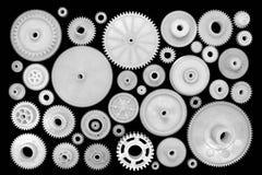 白色塑料齿轮和钝齿轮在黑背景 免版税图库摄影