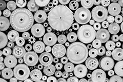 白色塑料齿轮和钝齿轮在黑背景 库存照片