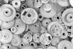 白色塑料齿轮和钝齿轮在黑背景 免版税库存图片