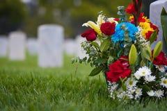 白色墓碑和花在公墓为阵亡将士纪念日 免版税库存图片