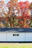 白色墙壁纹理房子,暗箱,在多彩多姿的叶子秋天森林背景的灵活的棕色瓦片  库存照片