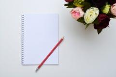 白色备忘录和一支红色铅笔在牡丹旁边 库存图片