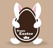 白色复活节兔子用巧克力复活节彩蛋 免版税图库摄影