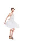 白色夏天礼服摆在的愉快的俏丽的妇女 免版税库存图片