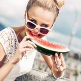 白色夏天礼服的女孩吃西瓜 免版税库存照片