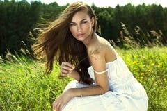 白色夏天礼服的被晒黑的妇女 免版税库存照片