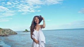 白色夏天礼服的,在蓝色海背景的笑的乐趣美女 股票录像