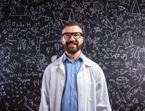 白色外套和镜片的老师反对大黑板机智 免版税库存照片