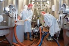 白色外套的两名微笑的工作者在啤酒厂工厂 免版税库存照片