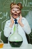 白色外套的女孩有有黑板的烧瓶的后边在科学实验室 免版税库存照片