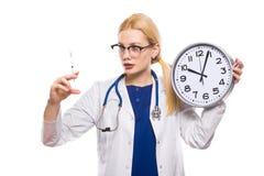 白色外套的妇女医生有时钟的 图库摄影