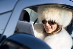 白色外套的妇女有ipad笑的 库存照片
