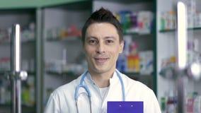 白色外套的微笑的男性药剂师在药房 股票视频