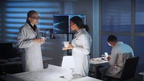 白色外套的混合的族种女性工程师谈论某事在现代实验室