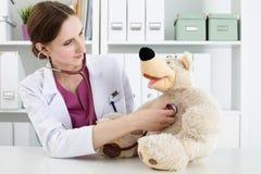 白色外套的美丽的微笑的女性医生审查玩具熊 免版税图库摄影