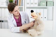 白色外套的美丽的微笑的女性医生审查玩具熊 免版税库存图片