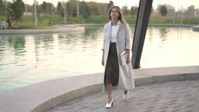 白色外套的美丽的白肤金发的妇女走在池塘附近的在秋天公园 股票录像