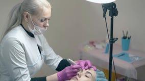 白色外套的美容师在眼眉做永久构成 股票录像
