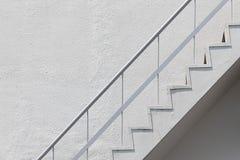 白色外部防火梯紧急楼梯侧视图与金属扶手栏杆栏杆和混凝土墙的 库存图片