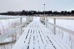 白色多雪的人行桥在冻水中 免版税库存图片