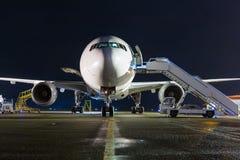 白色大型乘客飞机正面图有的在夜机场围裙的上的步 库存图片