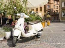 白色大黄蜂类比雅久,意大利被设计的滑行车,停放在咖啡馆附近 免版税库存照片