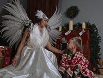 白色天使和小男孩在圣诞树附近 免版税图库摄影