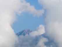 白色天堂般的云彩完全地围拢的山的上面 免版税库存照片