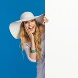 白色太阳帽子的笑的美丽的妇女在横幅后偷看 免版税库存照片