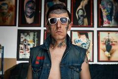 白色太阳镜的纹身花刺艺术家在演播室 库存图片