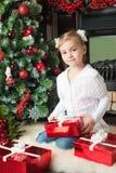 白色夹克的女孩有礼物的临近圣诞树 免版税库存图片