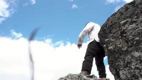 白色夹克身分的人在一座山的上面在蓝色,多云天空背景,底视图的 英尺长度 男 股票视频