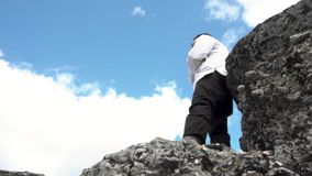 白色夹克身分的人在一座山的上面在蓝色,多云天空背景,底视图的 英尺长度 男 影视素材