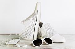 白色女性鞋子、太阳镜和一个巧妙的电话有耳机的 图库摄影