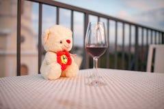 白色女用连杉衬裤在杯红葡萄酒旁边涉及在咖啡馆的桌 特写镜头 库存图片