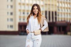 白色女衬衫和被剥去的牛仔裤的年轻时尚妇女走在城市街道的 库存图片