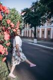 白色女衬衫和裙子的美丽的肉欲的深色的少妇有接近英国兰开斯特家族族徽的花的 她在红色玫瑰丛附近站立 免版税库存图片
