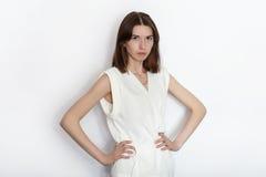 白色女衬衫实践的摆在的年轻美丽的深色的初学者模型妇女显示在白色墙壁演播室背景的情感 图库摄影