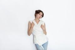 白色女衬衫实践的摆在的年轻美丽的深色的初学者模型妇女显示在白色墙壁演播室背景的情感 库存照片