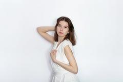 白色女衬衫实践的摆在的年轻美丽的深色的初学者模型妇女显示在白色墙壁演播室背景的情感 免版税库存图片
