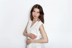 白色女衬衫实践的摆在的年轻美丽的深色的初学者模型妇女显示在白色墙壁演播室背景的情感 免版税库存照片