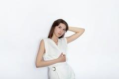 白色女衬衫实践的摆在的年轻美丽的深色的初学者模型妇女显示在白色墙壁演播室背景的情感 库存图片