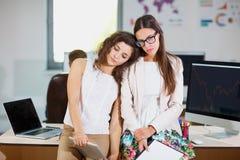 白色女衬衫的两个年轻企业女孩在办公室疲乏 图库摄影