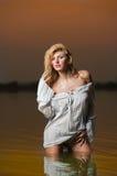 白色女衬衫的性感的白肤金发的妇女在河水 库存照片