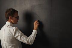白色女衬衫的老师在黑板 库存图片